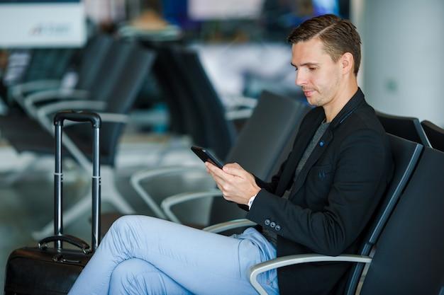 Junger mann mit mobiltelefon nach innen im flughafen. junger mann mit smartphone am flughafen beim warten auf das verschalen.