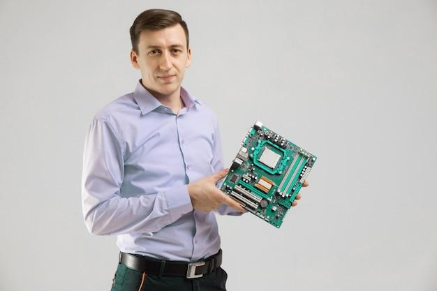 Junger mann mit motherboard in seinen händen ist lokalisiertes licht