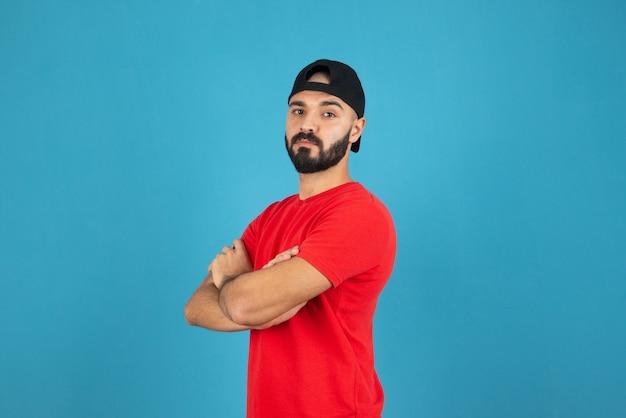 Junger mann mit mütze mit rotem t-shirt, das mit verschränkten armen steht.