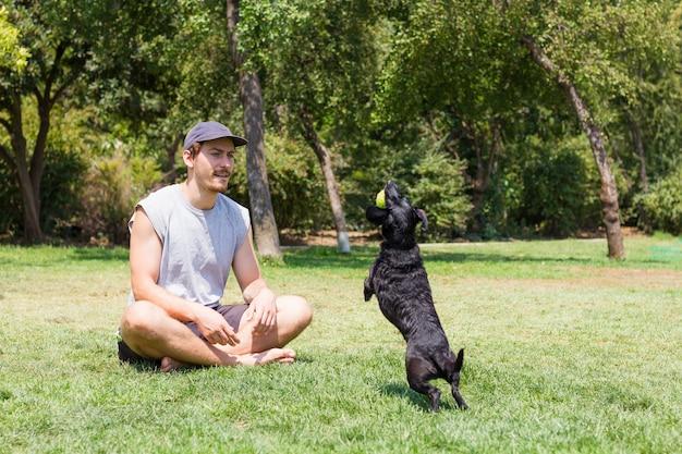 Junger mann mit mütze sitzt auf gras und schwarzer hund springt mit tennisball auf den mund