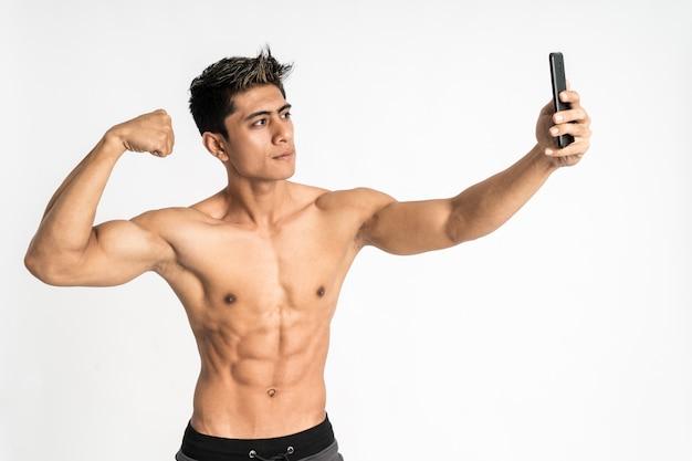 Junger mann mit muskulösem körper, der ein smartphone für selfie mit einer hand hält, zeigt muskulösen bizepsstand, der nach vorne zeigt und ein telefon betrachtet