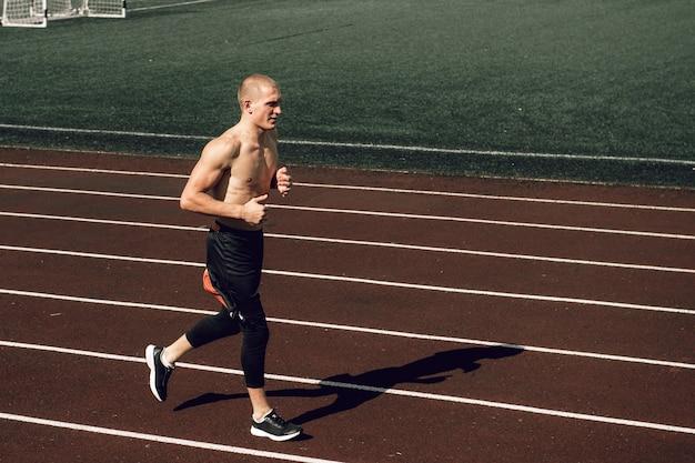 Junger mann mit nacktem oberkörper athletischer körper, der auf der stadionbahn läuft
