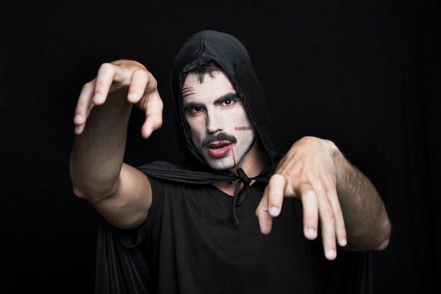 Junger mann mit narben auf blassem gesicht in halloween-kostüm, das im studio aufwirft