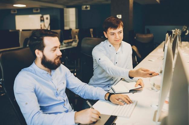 Junger mann mit notizbuch, das auf computermonitor für kollegen mit grafiktablett zeigt, während an projekt im büro arbeitet. kollegen, die an designprojekt zusammen arbeiten