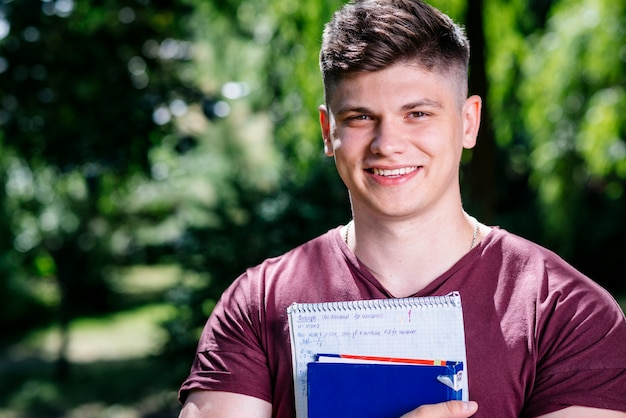 Junger mann mit notizbuch und buch