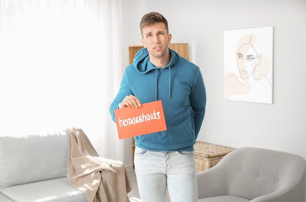 Junger mann mit papier mit text hemorrhoids zu hause