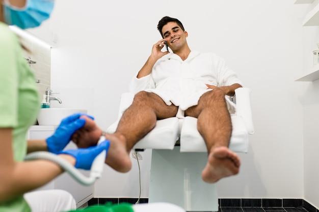 Junger mann mit pediküre-behandlung in einem modernen schönheitssalon.