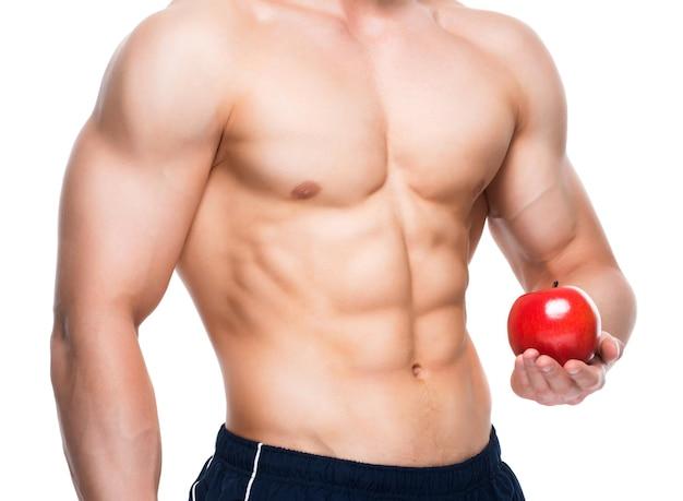 Junger mann mit perfektem körper, der roten apfel in seiner hand hält