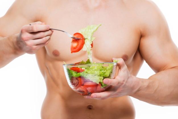 Junger mann mit perfektem körper hält salat - lokalisiert auf weißer wand.