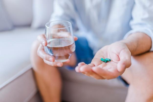 Junger mann mit pille und glas wasser zu hause, nahaufnahme