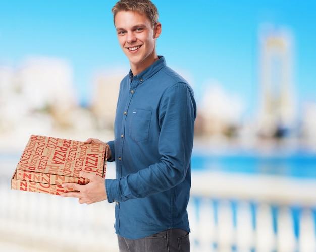 Junger mann mit pizzakartons