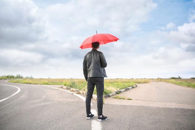 Junger mann mit regenschirm, der an der kreuzung steht. konzept der wahl