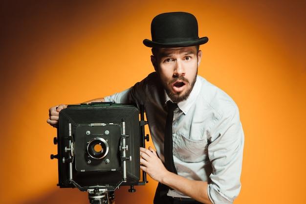 Junger mann mit retro-kamera