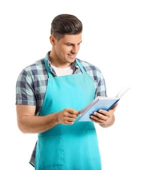 Junger mann mit rezeptbuch auf weiß