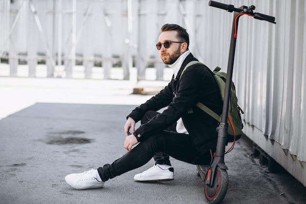 Junger mann mit roller, auf dem boden sitzend
