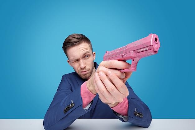 Junger mann mit rosa plastikspielzeug gunaiming beiseite, während am schreibtisch isoliert sitzen