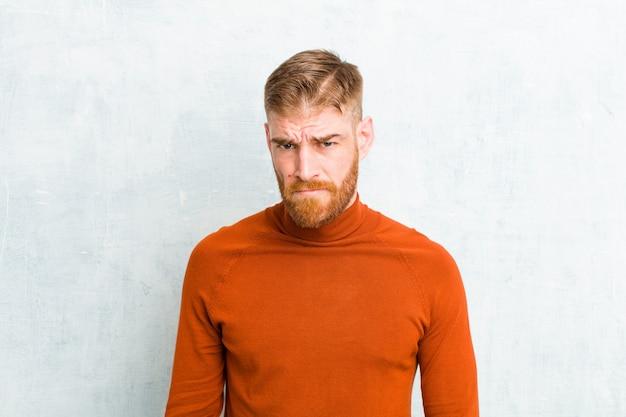 Junger mann mit rotem kopf, der einen rollkragen trägt und sich verwirrt und zweifelhaft fühlt, sich wundert oder versucht, eine entscheidung gegen eine betonwand zu treffen oder zu treffen