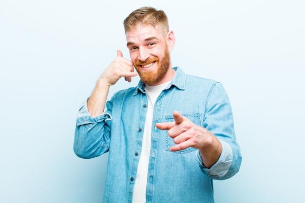 Junger mann mit rotem kopf, der fröhlich lächelt und auf die kamera zeigt, während sie einen anruf tätigen, den sie später gestikulieren und am telefon gegen weiches blau sprechen