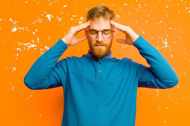 Junger mann mit rotem kopf, der konzentriert, nachdenklich und inspiriert aussieht, brainstorming und vorstellung mit den händen auf der stirn gegen grunge orange wand