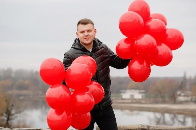 Junger mann mit roten luftballons in seinen händen