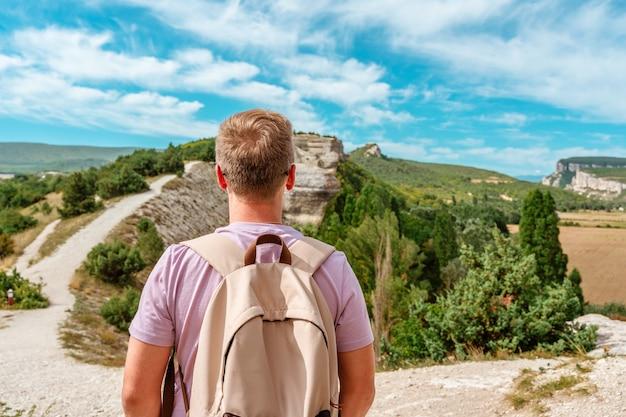Junger mann mit rucksack auf einem berghügel mit schönem himmel auf der krim