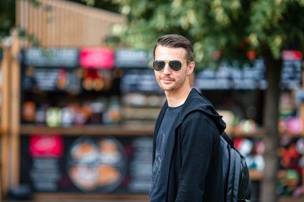 Junger mann mit rucksack auf straßenlebensmittelmarkt draußen