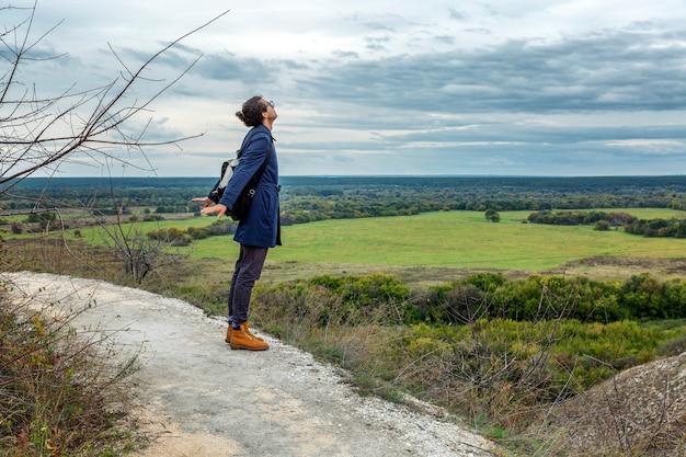 Junger mann mit rucksack in einer schönen herbstkarriere mit mehrfarbigem gras. wunderschöne landschaft.