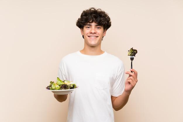 Junger mann mit salat über getrennter grüner wand