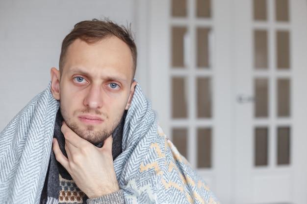 Junger mann mit schal, bedeckt seinen kopf mit einer decke, hält seinen hals wegen halsschmerzen