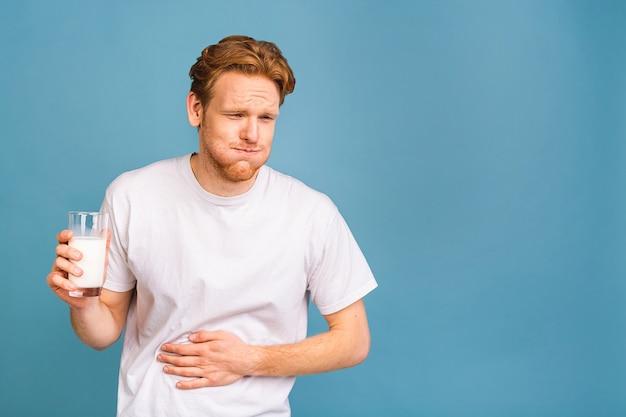 Junger mann mit schmerzen, der seinen schmerzenden magen hält. bauchschmerzen. laktose-milch-intoleranz.