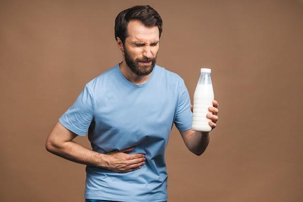 Junger mann mit schmerzen, der seinen schmerzenden magen isoliert auf beigem hintergrund hält. bauchschmerzen. laktose-milch-intoleranz.