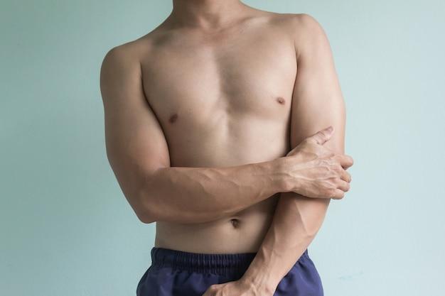 Junger mann mit schmerzlichem ellbogen