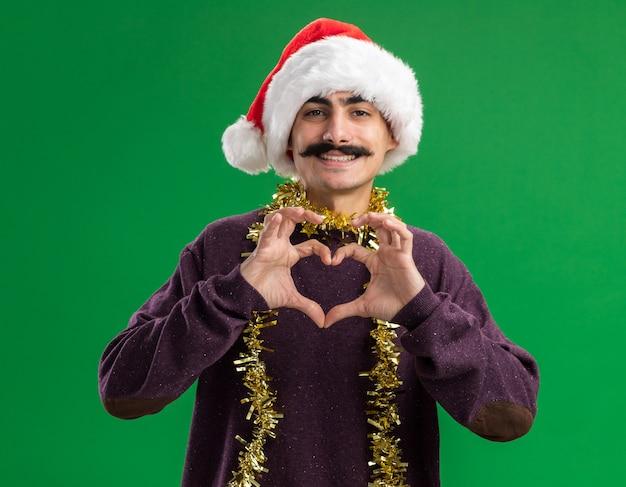 Junger mann mit schnurrbart, der weihnachtsmann-weihnachtsmütze mit lametta um seinen hals trägt und kamera mit glücklichem gesicht lächelnd tut, das herzgeste mit den fingern über grünem hintergrund stehend macht