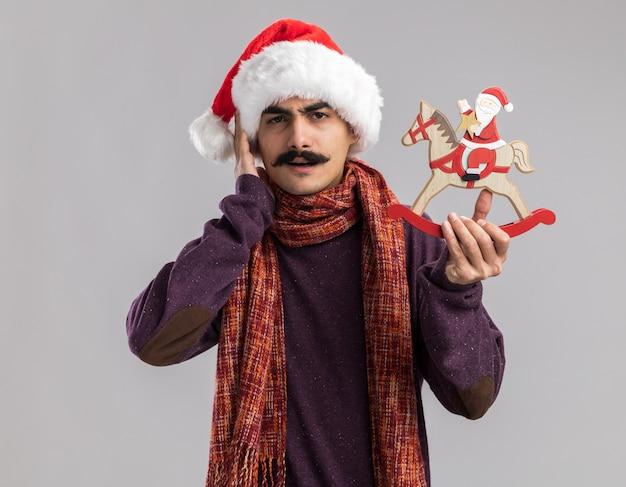 Junger mann mit schnurrbart, der weihnachtsmann-weihnachtsmütze mit warmem schal um seinen hals trägt, der weihnachtsspielzeug hält, das verwirrt schaut
