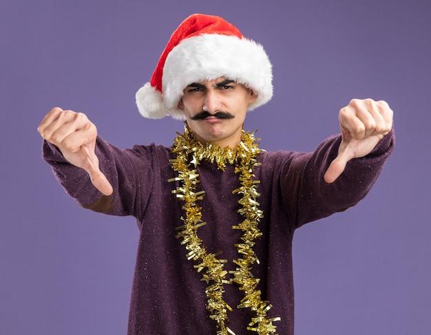 Junger mann mit schnurrbart, der weihnachtsweihnachtsmütze mit lametta um seinen hals trägt und kamera betrachtet, die unzufrieden zeigt, zeigt daumen nach unten stehend über lila hintergrund