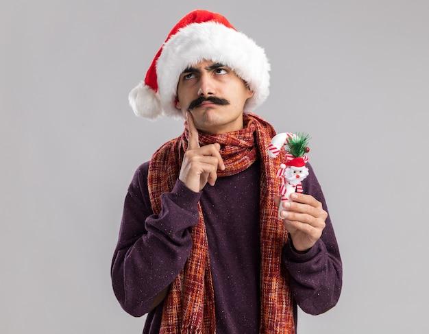 Junger mann mit schnurrbart, der weihnachtsweihnachtsmütze mit warmem schal um seinen hals trägt, der weihnachtszuckerstange hält, die verwirrt oben schaut