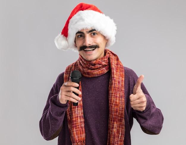 Junger mann mit schnurrbart, der weihnachtsweihnachtsmütze mit warmem schal um seinen hals trägt und mikrofon hält, das lächelnd fröhlich zeigt daumen zeigt