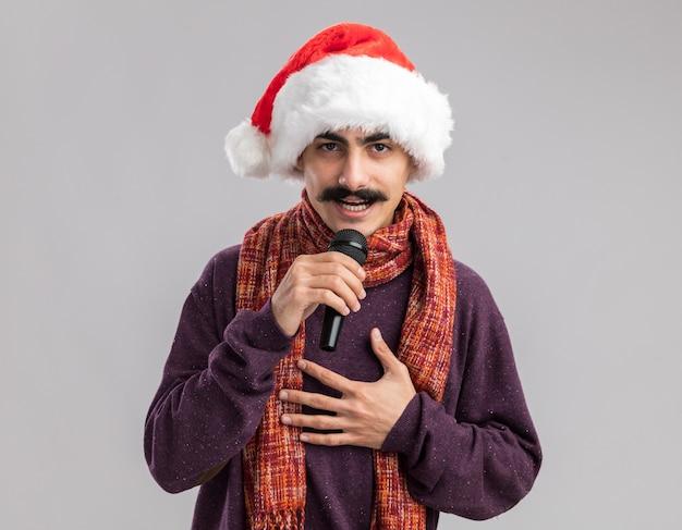 Junger mann mit schnurrbart, der weihnachtsweihnachtsmütze mit warmem schal um seinen hals trägt und mit dem mikrofon spricht, das mit lächeln auf gesicht schaut