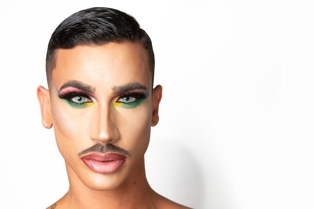 Junger mann mit schnurrbart und make-up mit glamourösem look auf weißem hintergrund