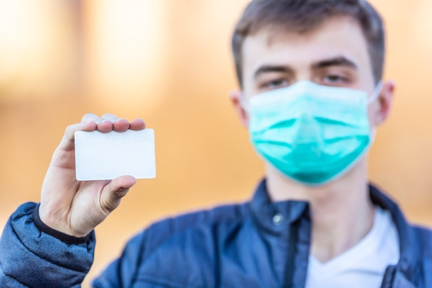 Junger mann mit schutzmaske im gesicht, der leere weiße karte hält. schutz vor virenstaub oder smog. coronavirus covid-19-konzept.
