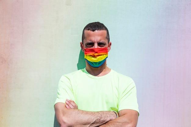 Junger mann mit schutzmaske und regenbogenflaggenarmband. lgtb.