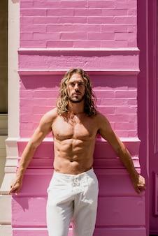 Junger mann mit sechs sätzen, der auf rosa wand aufwirft