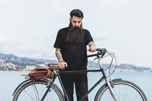 Junger mann mit seinem fahrrad, das nahe der küste steht