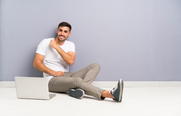 Junger mann mit seinem laptop, der ein der boden feiert einen sieg sitzt