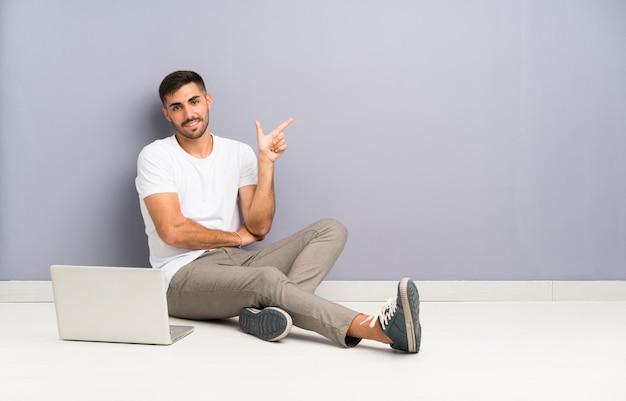 Junger mann mit seinem laptop, der einen der boden zeigt finger auf die seite sitzt