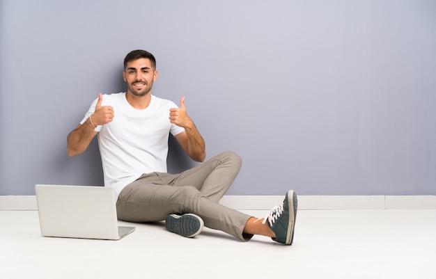 Junger mann mit seinem laptop, der eins der boden gibt daumen sitzt, up geste
