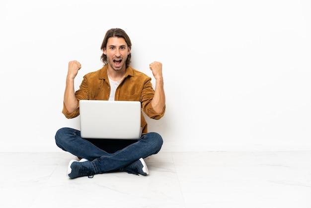 Junger mann mit seinem laptop sitzt auf dem boden und feiert einen sieg