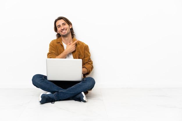 Junger mann mit seinem laptop sitzt auf dem boden und zeigt zur seite, um ein produkt zu präsentieren