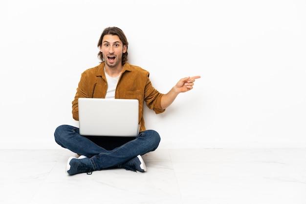 Junger mann mit seinem laptop sitzt überrascht auf dem boden und zeigt mit dem finger zur seite