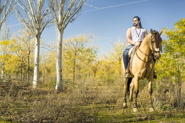 Junger mann mit seinem pferd, das durch das feld geht